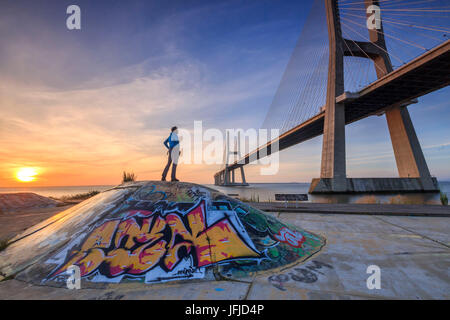 A tourist admires the majestic Vasco da Gama Bridge over the River Tagus Parque das Nações Lisbon Portugal Europe - Stock Photo