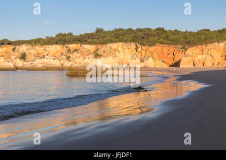 The newly risen sun shines on cliffs and reflected on the beach of Praia do Vau Algarve Faro District Portimao Portugal - Stock Photo