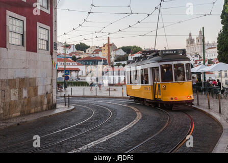 Romantic atmosphere in the old streets of Alfama with the castle in the background and tram number 28 Lisbon Portugal - Stock Photo
