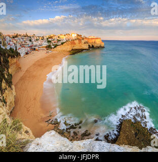 Panoramic view of Carvoeiro village surrounded by sandy beach and clear sea at sunset Lagoa Municipality Algarve - Stock Photo