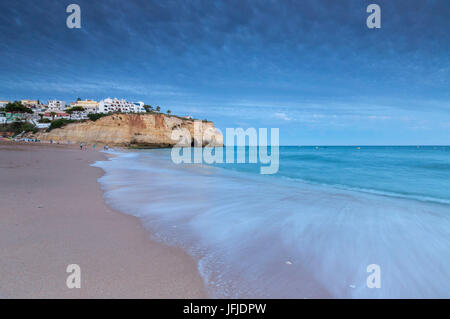 Ocean waves crashing on rocks and beach surrounding Carvoeiro village at sunset Lagoa Municipality Algarve Portugal - Stock Photo