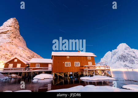 Starry night on the snowy peaks surrounded by the frozen sea and fishermen houses Reinevagen Bay Lofoten Islands - Stock Photo