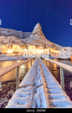 Starry night on the snowy peaks surrounded by the frozen sea Reinevagen Bay Nordland Lofoten Islands Norway Europe - Stock Photo