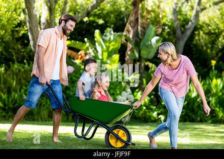 Parents pushing children sitting in wheelbarrow at yard - Stock Photo