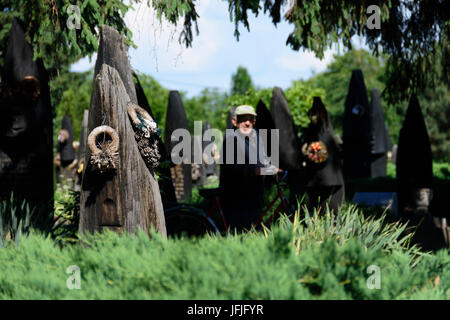 Szatmarczeke , Hungary. Wooden boat shaped gravestones on the cemetery. And old visitor with a bicycle. - Stock Photo