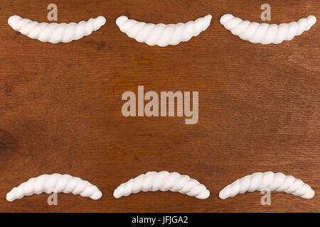 Luxury frame made of white stucco plaster, lying on a dark wood, with a place for your text - Stock Photo