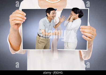 Composite image of woman holding a torn photo - Stock Photo