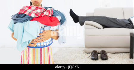 Composite image of tired woman holding full laundry basket - Stock Photo