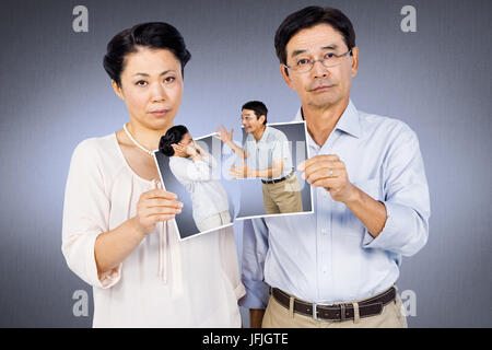 Composite image of asian couple holding a photo - Stock Photo