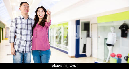 Composite image of happy couple standing together - Stock Photo