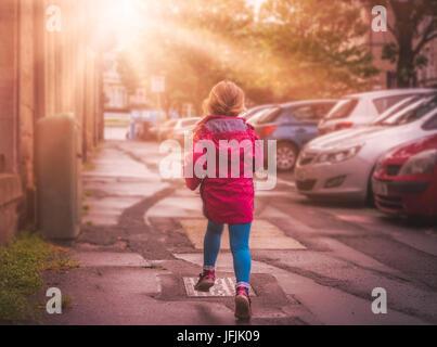 Little girl running in the morning in town street - Stock Photo