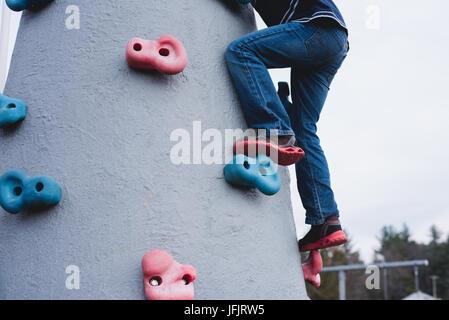 A boy climbs playground equipment. - Stock Photo