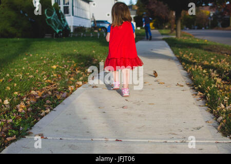 A young girl walks down a sidewalk from behind at sunset in the Fall wearing a red cape. - Stock Photo