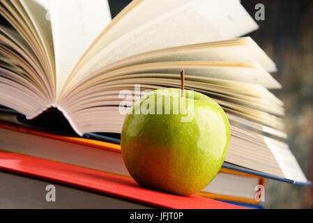 Composition with hardcover books and apple. - Stock Photo