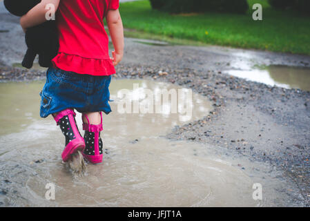A young girl walks into a mud puddle with rain boots on wearing red and holding a small stuffed dog. - Stock Photo