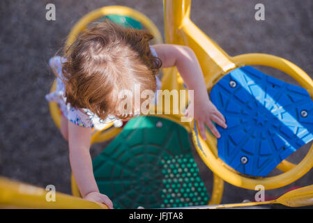 A young girl climbs on playground equipment in the sunlight wearing bright red shoes. - Stock Photo