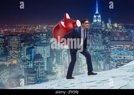 Businessman carrying the piggybank with savings - Stock Photo