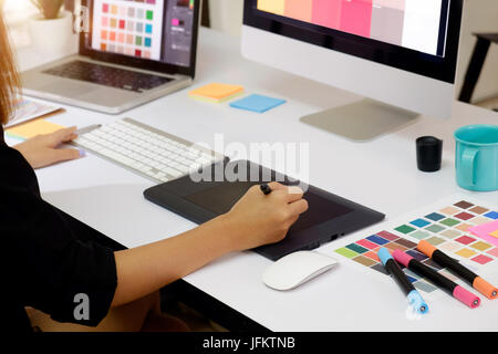 Side view of an artist drawing something on graphic tablet at the office. - Stock Photo