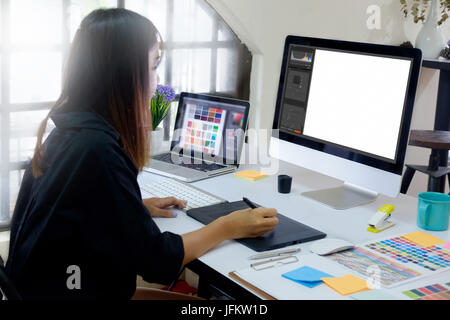 Young photographer and graphic designer at work in office.  Blank screen monitor for graphic display montage. - Stock Photo