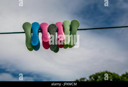 Close up of colourful clothes pegs on a washing line against the sky - Stock Photo
