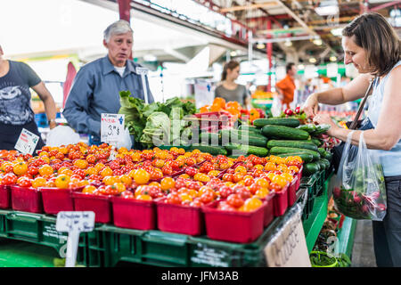 Montreal, Canada - May 28, 2017: Man selling produce by fruit stand with woman buying cucumbers at Jean-Talon farmers - Stock Photo