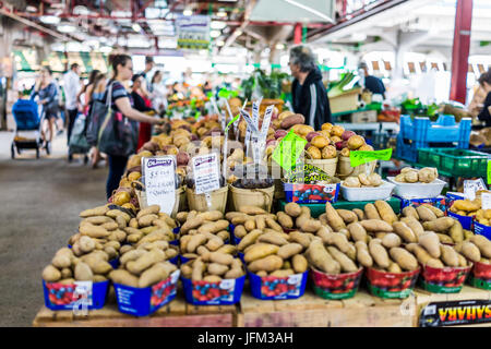 Montreal, Canada - May 28, 2017: Man selling produce by stands at Jean-Talon farmers market with displays - Stock Photo