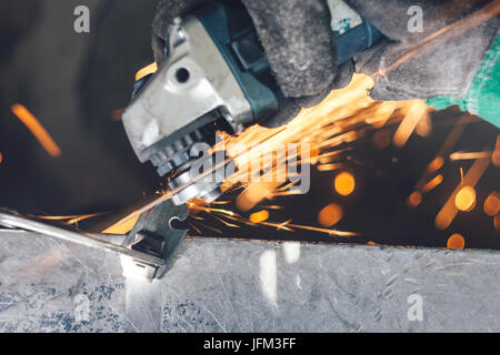 Cutting of curlicue hook using hand angle grinder and spreading sparks all around - Stock Photo