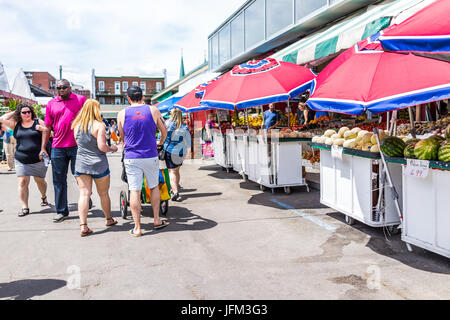 Montreal, Canada - May 28, 2017: People walking by produce vegetable stands outside during bright sunny day at Jean-Talon farmers market with displays