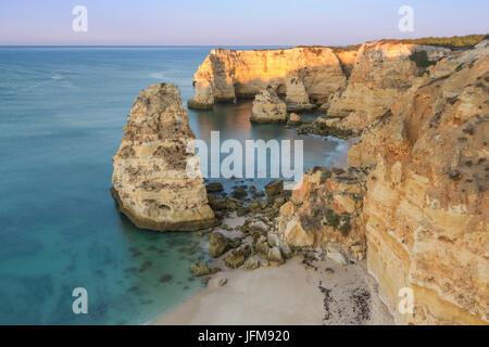 Sunrise on the cliffs and turquoise water of the ocean Praia da Marinha Caramujeira Lagoa Municipality Algarve Portugal - Stock Photo