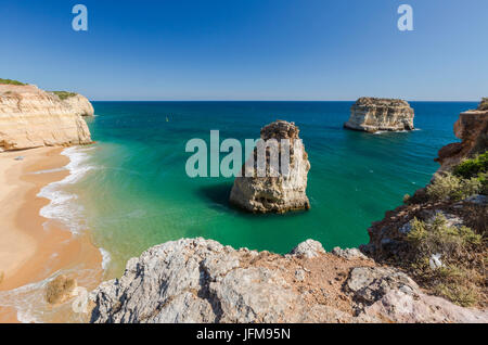 The ocean waves crashing on the sandy beach and the cliffs of Praia do Torrado Algarve Lagoa Faro District Portugal - Stock Photo