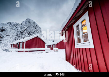 Clouds on the typical red houses of fishermen called Rorbu surrounded by snowy Hamnøy Lofoten Islands Northern Norway - Stock Photo