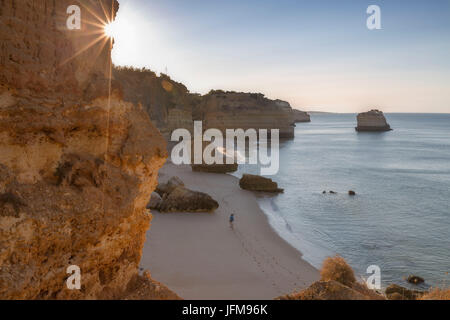 First rays of sun on the cliffs and turquoise water at Praia da Marinha Caramujeira Lagoa Municipality Algarve Portugal - Stock Photo