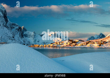 The blue color of dusk on the fishing village and the snowy peaks Kvalvika Andøya Reine Nordland Lofoten Islands - Stock Photo