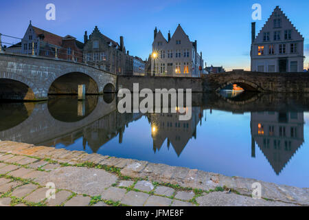 Dusk lights on the historic buildings of the city centre reflected in the typical canals Bruges West Flanders Belgium - Stock Photo