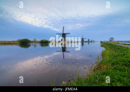 Traditional Dutch windmills reflected in the canal at dusk Kinderdijk Molenwaard South Holland The Netherlands Europe - Stock Photo