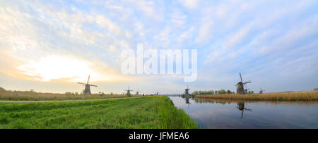 Panorama of the typical windmills reflected in the canals at dawn Kinderdijk Molenwaard South Holland The Netherlands - Stock Photo