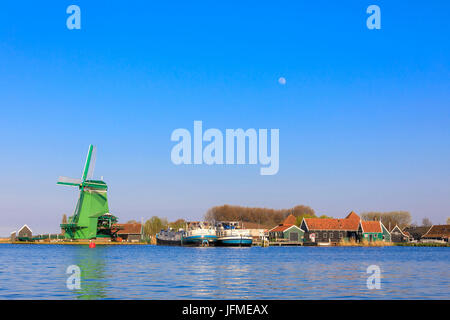 Typical windmill and boats in the fishing village of Zaanse Schans framed by river Zaan North Holland The Netherlands - Stock Photo