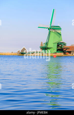 Typical windmill reflected in the blue water of river Zaan in spring Zaanse Schans North Holland The Netherlands - Stock Photo