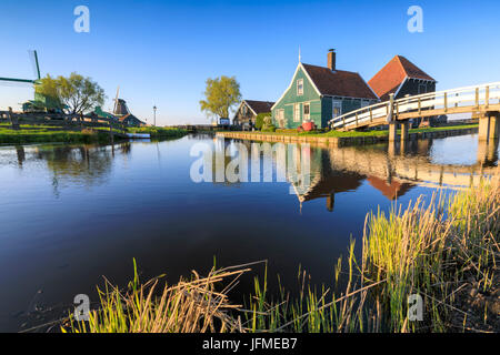 Wood houses on river Zaan framed by green meadows in the typical village of Zaanse Schans North Holland The Netherlands - Stock Photo