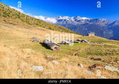 Alpine huts framed by snowy peaks of Bernina Group Arcoglio Alp Val Torreggio Malenco Valley Valtellina Lombardy - Stock Photo