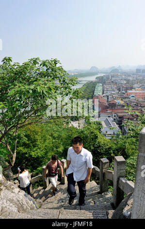 China, Guangxi Province, the city of Guilin in the middle of Karst mountain landscape, tourists climbing on the - Stock Photo