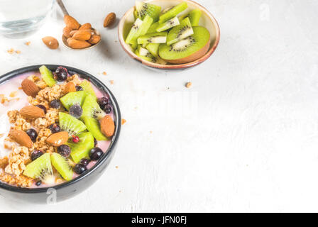 Healthy diet breakfast: smoothies bowl, with yogurt, fresh blueberries (black currant), kiwi, granola oatmeal, almond - Stock Photo