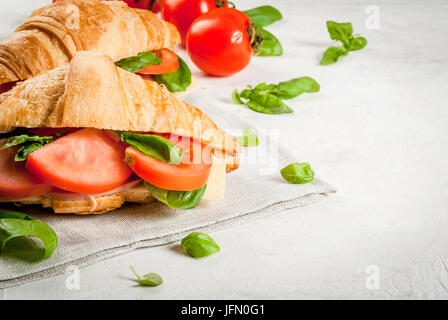 Light and hearty spring breakfast. Croissant with ham, cheese, fresh tomatoes and basil. On a white stone table, - Stock Photo