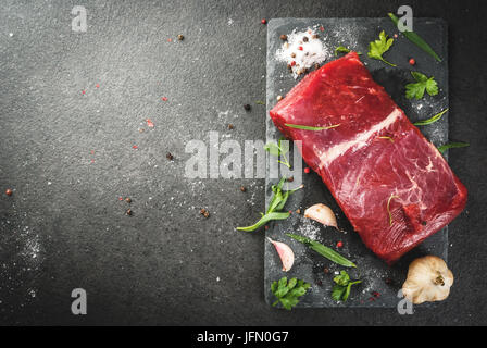 Fresh raw beef meat tenderloin on a slate cutting board on a black stone table. With spices (salt, pepper), garlic - Stock Photo