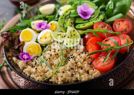 Diet menu. Healthy salad of fresh vegetables - tomatoes, avocado, arugula, egg, spinach and quinoa on a bowl - Stock Photo