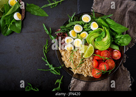 Diet menu. Healthy salad of fresh vegetables - tomatoes, avocado, arugula, egg, spinach and quinoa on bowl. Flat - Stock Photo