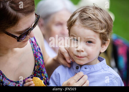 Mother comforting son after falling down and hurting face during walk in park. Boy eating cookie, senior grandmother - Stock Photo