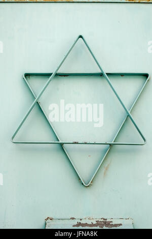 A cyan star of david made of metal attached to a local synagogue - Stock Photo