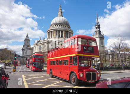 Red London buses passing St Paul's Cathedral, City of London, England, UK, GB - Stock Photo
