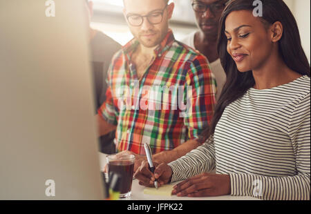 Young woman taking a note while the people looking at her in the office. - Stock Photo